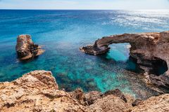 Beautiful natural rock arch near of Ayia Napa, Cavo Greco and Protaras on Cyprus island, Mediterranean Sea. Legendary bridge. Lovers. Amazing blue green sea and royalty free stock images