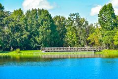 Beautiful natural scenery with autumn forest, wood bridge and blue lake at Celebration Town in Kissimmee area. Orlando, Florida. January 15, 2019. Beautiful stock photo