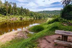 River landscape with a resting place to the forefront on the right. Beautiful natural scenery with river and forest along the banks of the river; River landscape stock photos