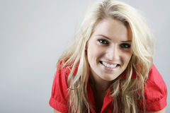Beautiful natural smiling blond woman. In a red blouse leaning towards the camera with a lovely beaming smile against a grey background with copyspace stock photography