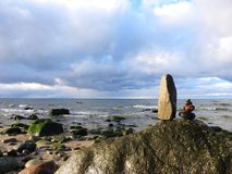 Beautiful natural stones tower on Baltic sea coast, Lithuania. Nice natural stones tower on Baltic sea coast and beautiful cloudy sky stock photo
