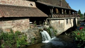Beautiful natural waterfall on small river in Alsace village stock video