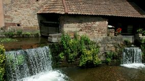 Beautiful natural waterfall on small river in Alsace village stock video footage