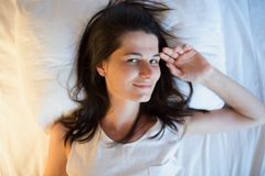 Beautiful natural young woman on the white bed. View from above. Beautiful natural young smiling woman on the white bed. View from above Stock Photos