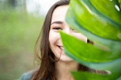 Beautiful natural young woman closeup behind big monstera leaf with green background in the woods stock photo
