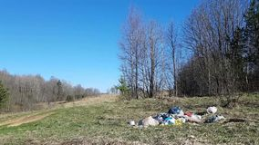 Beautiful nature-field, rural road and spring trees. Against the background of nature, a small mountain of garbage. Environmental pollution stock video