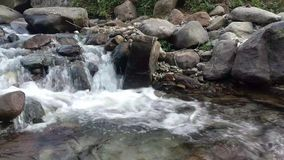 Beautiful nature with a fountain in India, Himalayas. stones, river bank, natural environment, stones inside, wet weather, cloudy, stock footage