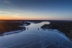 Beautiful nature and landscape at cold winter evening in Sweden Scandinavia Europe. Nice sunset and frozen ice lake. Shot with drone from above in sky. Calm stock photos