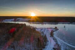 Beautiful nature and landscape at cold winter evening in Sweden Scandinavia Europe. Nice sunset and frozen ice lake. Shot with drone from above in sky. Calm stock photography