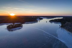 Beautiful nature and landscape at cold winter evening in Sweden Scandinavia Europe. Nice sunset and frozen ice lake. Shot with drone from above in sky. Calm royalty free stock photos