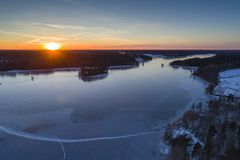 Beautiful nature and landscape at cold winter evening in Sweden Scandinavia Europe. Nice sunset and frozen ice lake. Shot with drone from above in sky. Calm stock photo