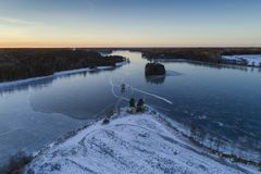 Beautiful nature and landscape at cold winter evening in Sweden Scandinavia Europe. Nice sunset and frozen ice lake. Shot with drone from above in sky. Calm royalty free stock photo