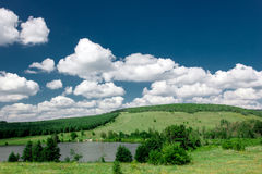 Beautiful nature landscape. Green tree hills and blue cloudy sky Stock Photos