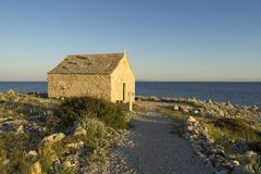 Beautiful nature and landscape photo of church and coast at Adriatic Sea in Croatia. Nice outdoors image at sunset. Calm, peaceful spring evening royalty free stock photography