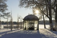 Beautiful nature and landscape photo of cold sunny winter day in Sweden Scandinavia. Nice clear blue sky at morning. Snow, small glass house and ice lake. Calm stock photography