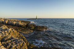 Beautiful nature and landscape photo of lighthouse and coast at Adriatic Sea in Croatia. Nice outdoors image at sunset. Calm, peaceful spring evening royalty free stock photos
