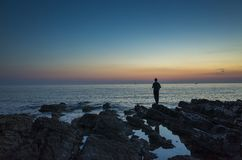 Beautiful nature and landscape photo of male man standing outdoors close the ocean at dusk evening stock images
