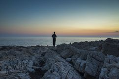 Beautiful nature and landscape photo of male man standing outdoors close the ocean at dusk evening stock photos