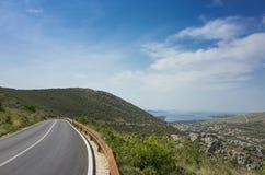 Beautiful nature and landscape photo of road in Dalmatia Croatia Europe. Nice sunny spring day with blue sky and mountains at horizon. Calm, peaceful, joyful Stock Image