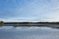 Beautiful nature and landscape photo of sunny spring day in Sweden Scandinavia Europe. Nice blue sky, lake with ice and wooden bridge. Calm, peaceful and happy royalty free stock photos