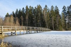 Beautiful nature and landscape photo of sunny spring day in Sweden Scandinavia Europe. Nice blue sky, lake with ice and wooden bridge. Calm, peaceful and happy royalty free stock image