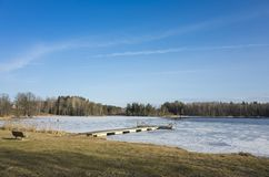 Beautiful nature and landscape photo of sunny spring day in Sweden Scandinavia Europe. Nice blue sky, lake with ice and wooden bridge. Calm, peaceful and happy stock photo
