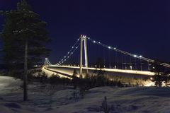 Beautiful nature and landscape photo of Sweden Scandinavia with the bridge Hoga Kusten. Nice cold winter night with snow on ground and stars in blue sky. Calm stock photo