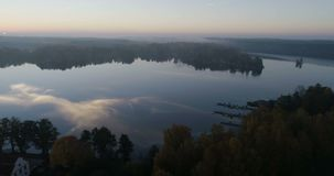 Beautiful nature and landscape video of sunrise at Djolo in Katrineholm, Sweden. Nice misty autumn morning at the lake, Filmed with drone from sky stock footage