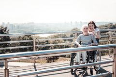 Positive disabled woman being outside. Beautiful nature. Positive nice disabled women smiling and being in the positive mood while being outside Stock Photo