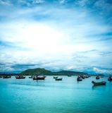 Beautiful nature seascape. The quiet sea with mountains at daytime. Many fishing boats Floating in the bay of the sea in southern Thailand royalty free stock photo