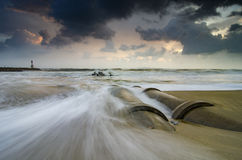Beautiful nature, soft waves hitting concrete drainage pipe on the beach Royalty Free Stock Photos