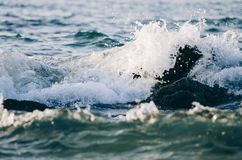 Splashing wave while hitting the rock at the beach Royalty Free Stock Photo