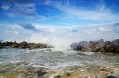 Beautiful nature, splashing wave while hitting the rock at the beach. cloudy blue sky Stock Image