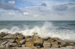 Beautiful nature, splashing wave while hitting the rock at the beach. cloudy blue sky Stock Photo
