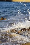 Splashing wave while hitting the rock at the beach Royalty Free Stock Photos