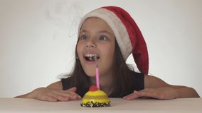 Beautiful naughty girl teenager in a Santa Claus hat blows out a candle on a festive cake on white background. Beautiful naughty girl teenager in a Santa Claus Stock Images