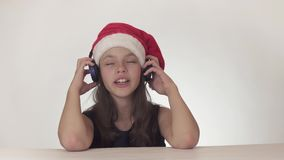 Beautiful naughty girl teenager in a Santa Claus hat listens to music on headphones and sings along on white background stock footage