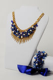 Beautiful navy blue necklace, gold chain and bracelet with big satin ribbon on a mannequin in front of white background Stock Image