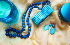 Beautiful necklace of dark faceted agate, turquoise bracelet and earrings and other blue objects on yellow shiny silk royalty free stock images