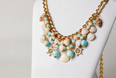 Beautiful necklace in marine style with seashells, and little wheels Stock Images