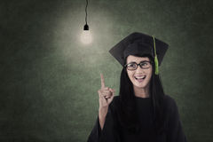 Beautiful nerd in graduation gown have idea Stock Images