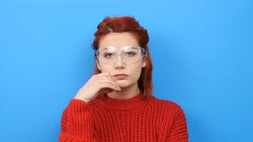 Beautiful nerd woman puts chemist glasses on. And looks at the camera. Blue background stock video