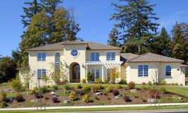 Beautiful New Home. Newly constructed upscale home complemented by foreground flowers and deep blue sky stock photography