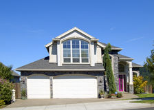 Beautiful New Home. Newly constructed upscale home complemented by foreground flowers and deep blue sky stock image