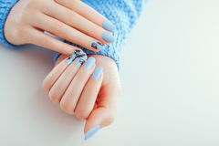 Beautiful New Year manicure. Blue nails with black design and rhinestones. Space stock photography
