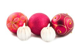 Beautiful New Year's spheres and candles. Red beautiful New Year's spheres ornament fur-trees and decorative burning candles on white background Royalty Free Stock Photos