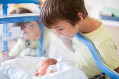 Beautiful newborn baby boy, laying in crib in prenatal hospital,. His brothers looking at him with adore Royalty Free Stock Photo