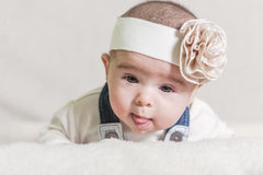 Beautiful newborn baby girl. With bow, lying in her bed and smiling Royalty Free Stock Image
