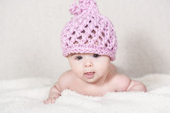 Beautiful newborn baby girl. With funny handmade pink hat, lying in her bed and smiling Royalty Free Stock Image