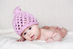 Beautiful newborn baby girl. With funny handmade pink hat, lying in her bed and smiling Royalty Free Stock Photo